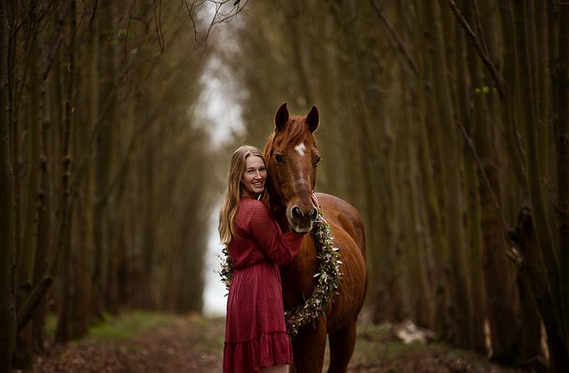 Pferd und Mädchen im Wald kuscheln